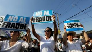 "People hold signs reading ""No to fraud"" and ""(Election) Run-off now"" as they protest near the electoral council in Guayaquil, Ecuador February 20, 2017."