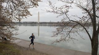 Woman jogs in DC with Washington Monument in background