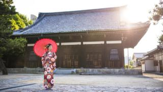 A woman stands in traditional clothing outside a Japanese temple