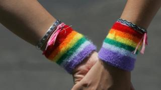 Women wearing rainbow wristbands hold hands