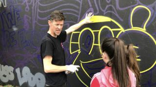 Donal O'Doherty teaching a girl how to spraypaint
