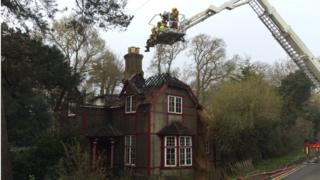 Burnt out house with fire-fighters on platform above