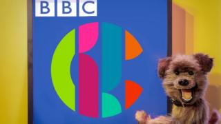 The Hacker T Dog puppet and the CBBC logo
