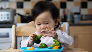 Baby girl eating vegetables
