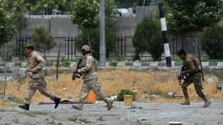 Afghan security personnel run at the scene of a suicide attack by Taliban militants on the Afghan parliament building in Kabul on 22 June 2015