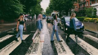 Jenna walks bare foot across Abbey road crossing.