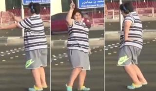 Three collaged screengrabs show a teen wearing a stripey shirt and sport shorts at various stages of doing the popular Macarena dance in a Saudi street