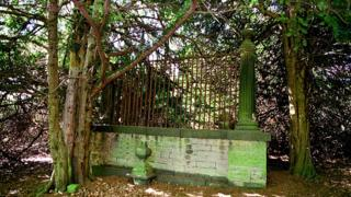 Gated grave surrounded by trees