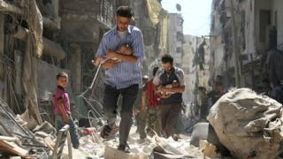 Syrian men carrying babies make their way through the rubble of destroyed buildings following a reported air strike on the rebel-held Salihin district of the northern city of Aleppo (11 September 2016)