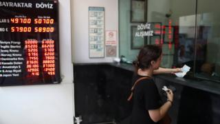A woman exchanges money at a currency exchange office in Istanbul, Turkey.
