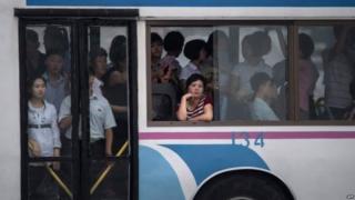 उत्तर कोरिया में एक बस में बैठे यात्री