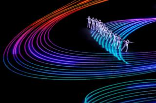 Artists perform around projected lines of coloured light