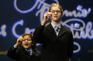 """School children sing out the number of the top prize of Spain's Christmas lottery known as """"El Gordo"""""""