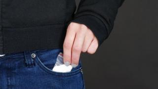 Mulher retira drogas do bolso