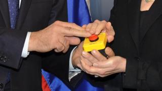 The hands of US Secretary of State Hillary Clinton and Russian Foreign Minister Sergei Lavrov rest on a red button marked 'reset' in English and 'overload' in Russian