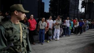 People line up to get into a Banco Mercantil branch in Caracas, Venezuela December 13, 2016.