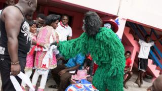 A man dressed as a green monkey shows his cheeky side at a traditional Fancy Dress festival in Winneba, Ghana.