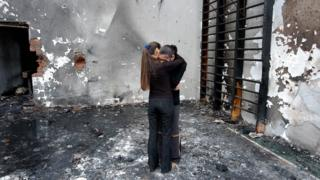 Two girls hug while they stand at the destroyed school gym in Beslan, North Ossetia, 05 September 2004