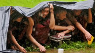 Buddhist monks take shelter under a tarpaulin sheet