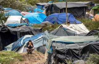 Человек на корточках на фоне самодельной палатки