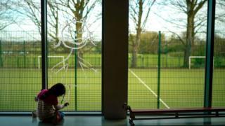 School pupil drawing on window