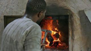 A man tends the bakery fire