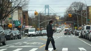 A man wearing a mask walks over a road in Brooklyn, New York