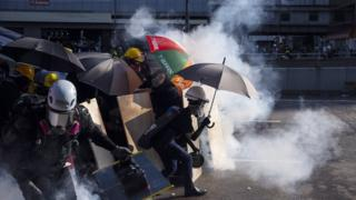 Protesters react as Hong Kong police fire tear gas in the Admiralty district (5 August)