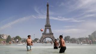 People bathe in the Trocadero Fountain in front of the Eiffel Tower in Paris