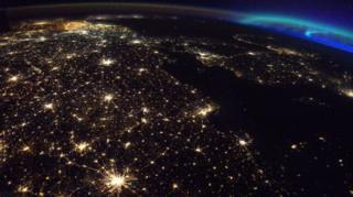 จุดสีส้มสว่างไสวด้านบนของภาพคือประเทศเบลเยียม ส่วนแสงเหนือสีฟ้าเขียวงดงามปรากฏอยู่ที่มุมขวาของภาพ