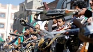 Houthi supporters hold up their weapons as they attend a gathering ahead of a rally celebrating the birthday of thee Prophet Mohammed in Sanaa, Yemen (28 November 2017)