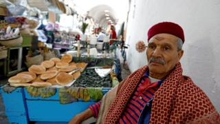 A street vendor poses with a machmoum, a bouquet of jasmine, behind his ear at the Kasbah souk in the old town of Tunis, Tunisia