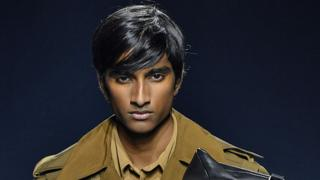 20-year-old Jeenu Mahadevan wears a brown trenchcoat as he models for Givenchy at Paris Fashion Week in 2018
