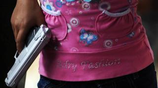 Una niña con una pistola de plástico