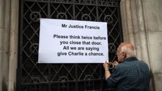 Человек прикрепляет плакат в поддержку Чарли Гарда на дверь суда