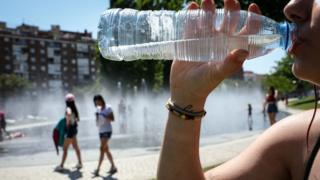 A woman drinking water during a heatwave