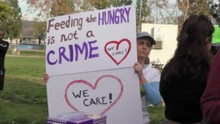 A woman holds a sign that reads 'Feeding the Hungry is not a Crime'