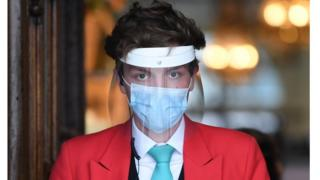 An employee wearing personal protective equipment (PPE) including a face mask and a visor staffs the entrance to up-scale department store Fortnum and Mason on Piccadilly in central London.