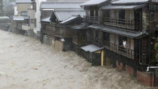 Men watch from their balcony as a river floods their home in Ise