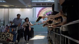 Người biểu tình phát giấy cho hành khách ở sân bay ngày 9/8
