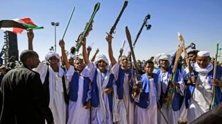 "Supporters of Sudan""s President Omar al-Bashir raise up sticks and swords in salute as they gather during a rally for him in the Green Square in the capital Khartoum on January 9, 2019"