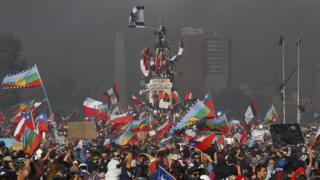 Protesters shout slogans and wave flags of Chile and the Mapuche people during a national strike and general demonstration called by different workers' unions on 12 November, 2019 in Santiago, Chile.