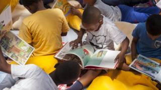 Niños leen en una actividad de la organización Pasa la Cebra.