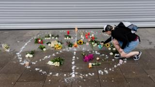 A woman places a candle at a makeshift memorial arranged like a peace sign at the scene of a knife attack in the northern German city of Hamburg, 29 July 2017