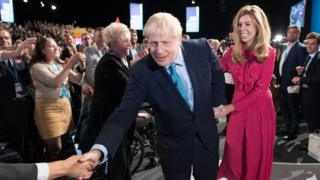 Prime Minister Boris Johnson leaves the stage with his partner Carrie Symonds after delivering his speech during the Conservative Party Conference at the Manchester Convention Centre.