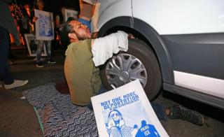 Protester locks himself to a van carrying Guadalupe Garcia de Rayos that is stopped by protesters in Phoenix, Arizona. 8 Feb 2017
