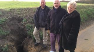 Nick Rix, Roger and Janet Dunnet (left to right) stand next to the badger sett in Flowton Road, Somersham
