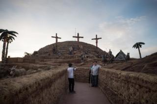 Tourists take photographs in front of three crucifixes