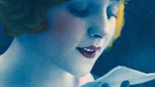 Una mujer peinada y maquillada al estilo de los años 20 leyendo una carta