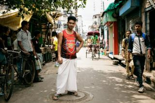 A stallholder in the backstreets of Kolkata wears an Arsenal top alongside his local attire